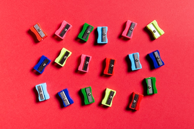 Colorful pencil sharpeners on red table