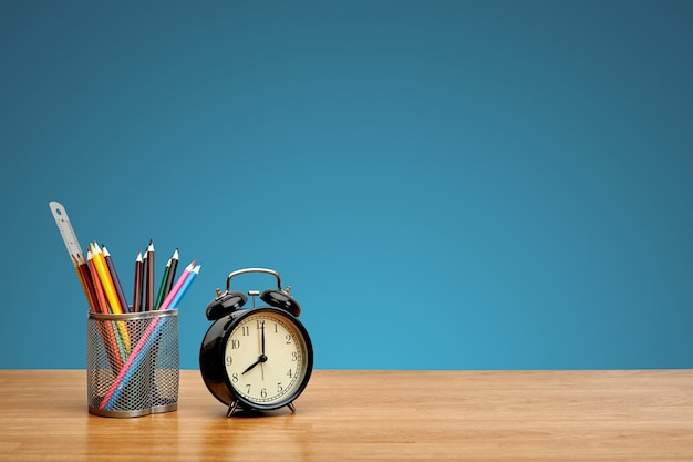 Colorful pencils and alarm clock on a table