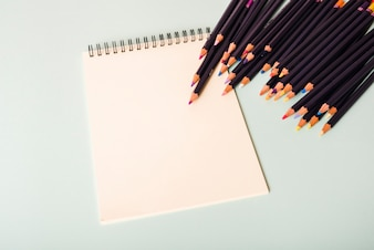 Colorful pencils and blank white spiral notepad on white background