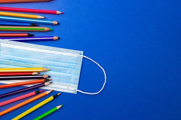 Цветные карандаши и медицинская маска для лица