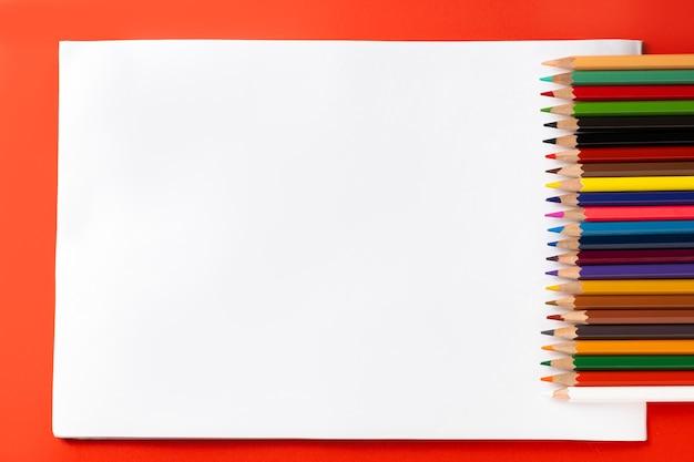 カラフルな鉛筆と赤い背景に描くためのアルバムのテキストの場所。教育の概念と学校に戻る概念。上面図。テキストの場所