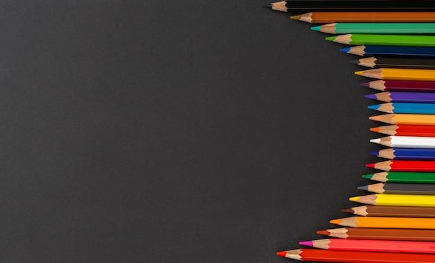 カラフルな鉛筆と黒の背景にテキストの場所。教育の概念と学校に戻る概念。上面図。テキストの場所