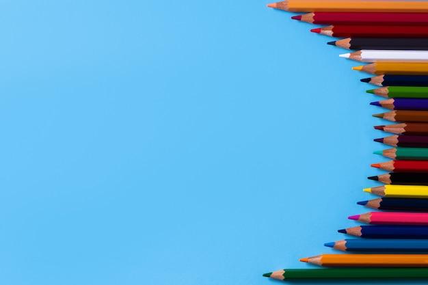 カラフルな鉛筆と青い背景のテキストの場所。教育の概念と学校に戻る概念。上面図。テキストの場所。