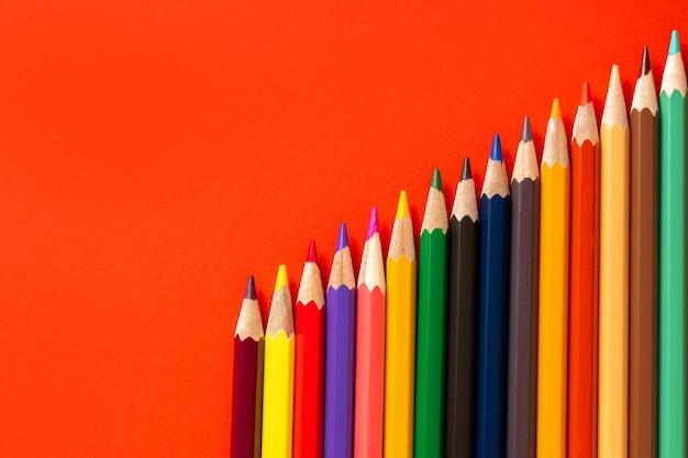 カラフルな鉛筆と赤い背景のテキストの場所。教育の概念と学校に戻る概念。上面図。テキストの場所