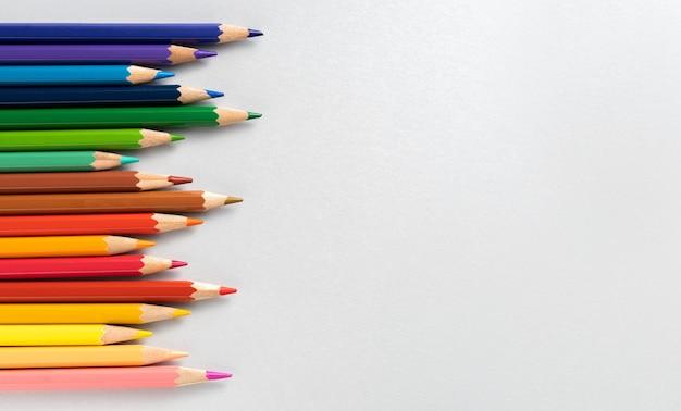 カラフルな鉛筆と白い背景のテキストの場所。教育の概念と学校に戻る概念。上面図。テキストの場所