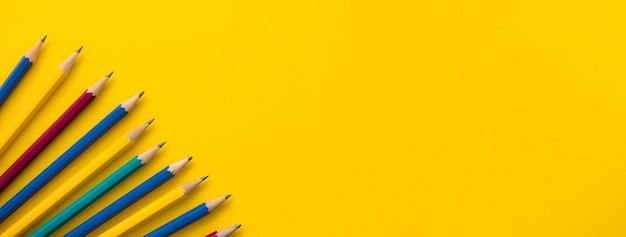 Красочные карандаши на границе баннера желтый фон