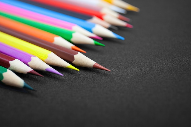 Colorful pencils on black background with copy space.