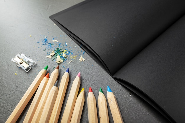 Colorful pencils and black book