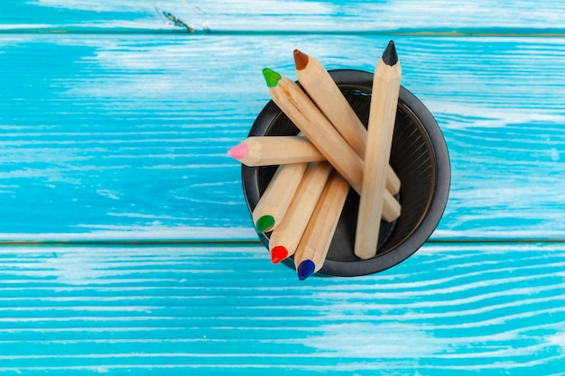 Colorful pencils on a bright blue wooden background