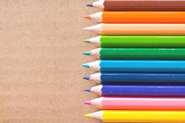 Colorful pencils on brown background