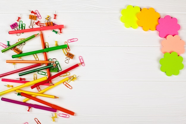 Colorful pencils and felt-tip pens, notepaper and stationery on white wooden background.