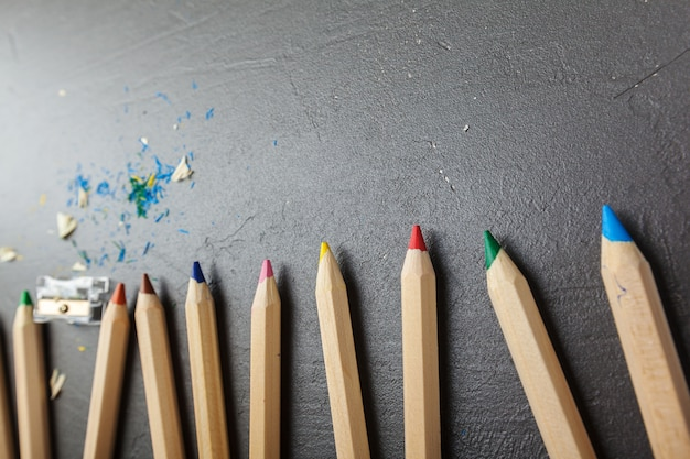 Colorful pencils on gray stone
