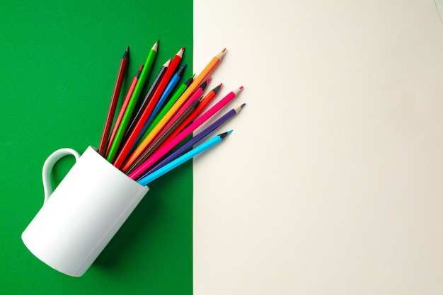 Colorful pencils on green and white paper background top view copy space