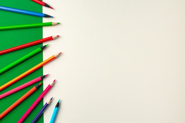 Colorful pencils on green and white paper background top view