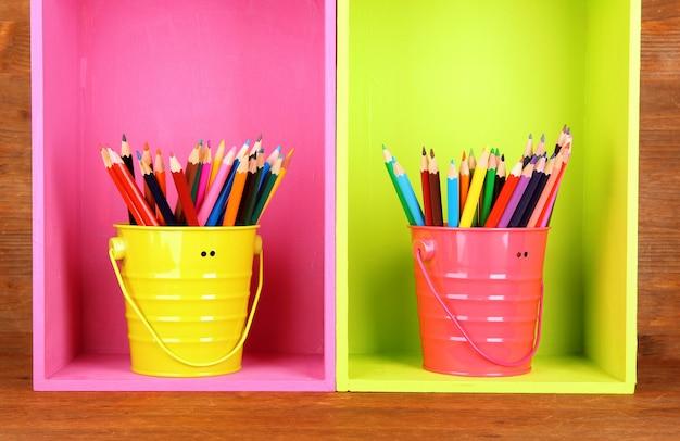 Красочные карандаши в ведрах на полках на деревянных фоне