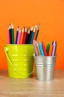 Красочные карандаши в двух ведрах на столе на оранжевом фоне