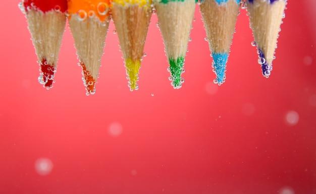 赤い背景に泡と水中のカラフルな鉛筆