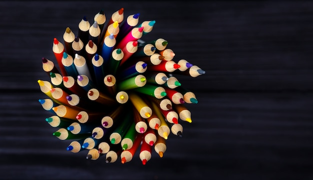 Colorful pencils in metal holder on black wooden table
