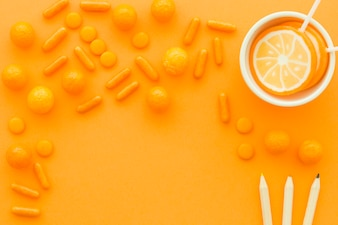 Colorful pencils near lollipops and candies on orange background