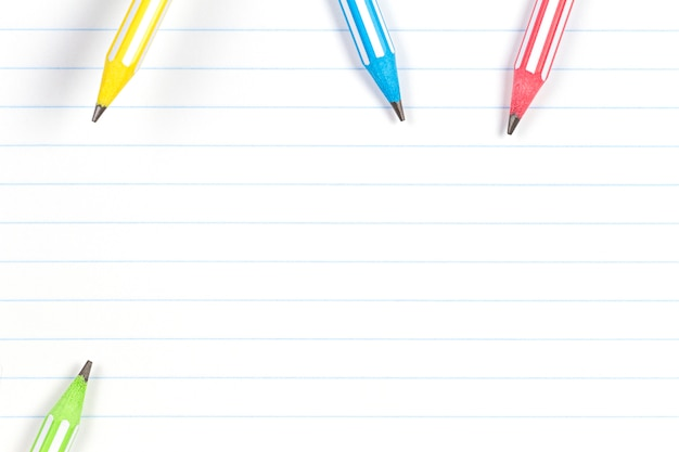Colorful pencils on notebook lined paper background with copy space. back to school, education, learning concept