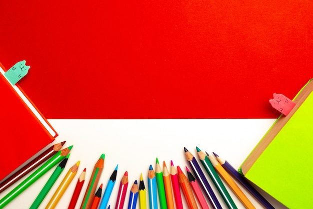 Colorful pencils and notepads on paper background top view, copy space