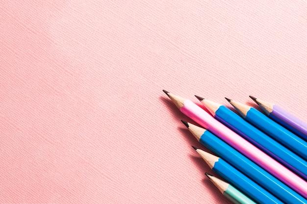 パステルピンクの背景にカラフルな鉛筆