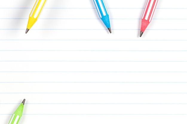 노트북에 다채로운 연필 줄이 그어진 된 종이 배경 복사 공간. 학교, 교육, 학습 개념으로 돌아 가기