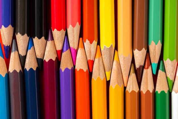 赤い背景にカラフルな鉛筆。鉛筆の背景、教育の概念と学校に戻る概念。上面図