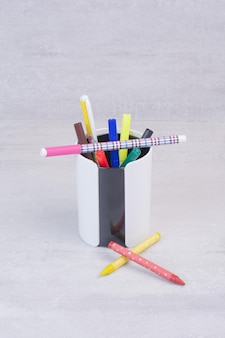 Matite colorate in astuccio sul tavolo bianco.
