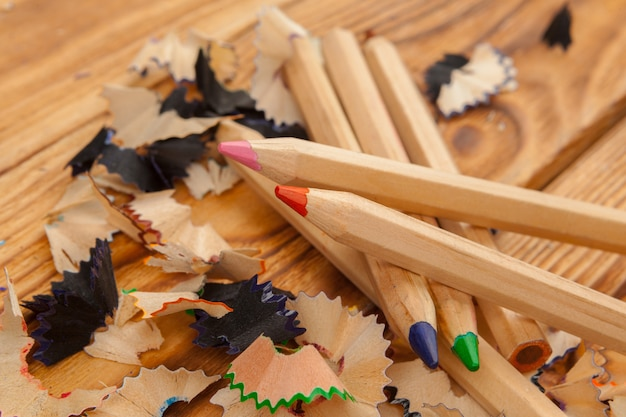 Colorful pencils and pencil cuts on wooden close up
