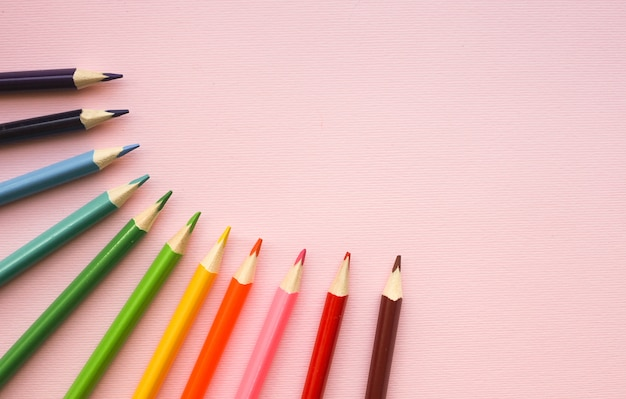 Colorful pencils of rainbow colors on pink pastel