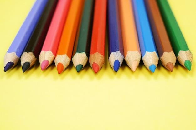Красочные карандаши сырые на желтом фоне, крупным планом