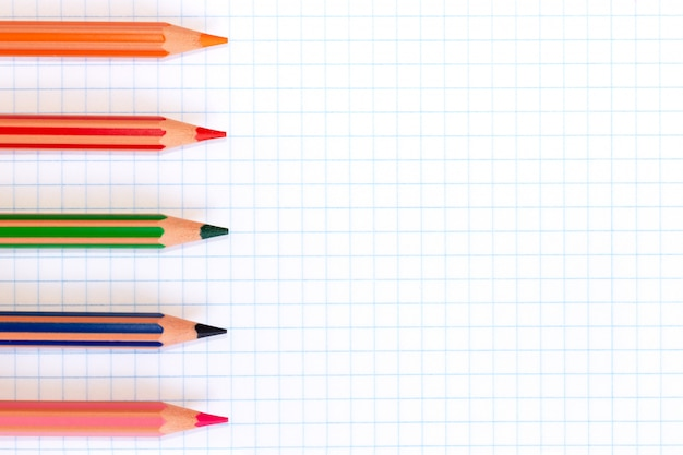 Colorful pencils of red, green, orange, pink and blue colors on a checkered exercise book