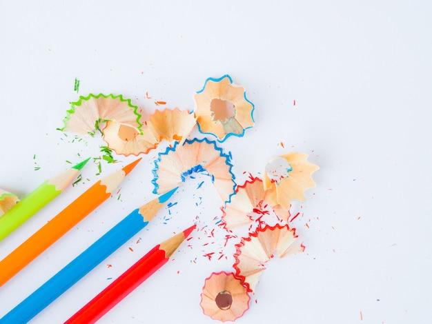 흰색 바탕에 화려한 연필 부스러기와 다채로운 연필. 학교 개념으로 돌아 가기