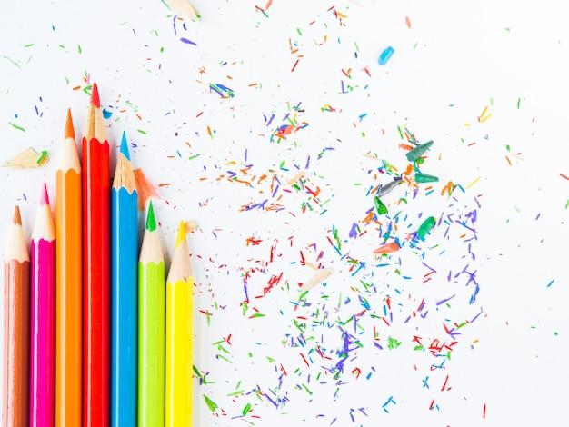 흰색 바탕에 화려한 연필 부스러기와 다채로운 연필.