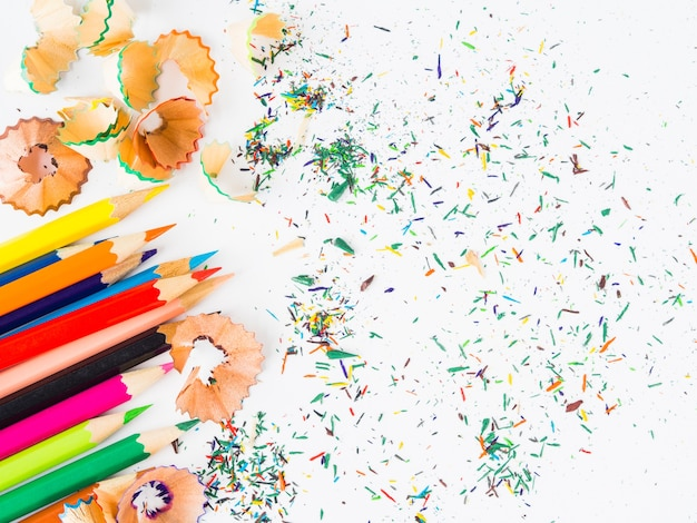 Colorful pencils with colorful pencil shavings on white background