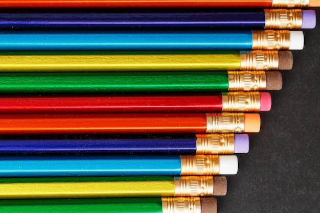 Красочные карандаши с ластиками подряд на черном фоне. вид сверху, свободное место
