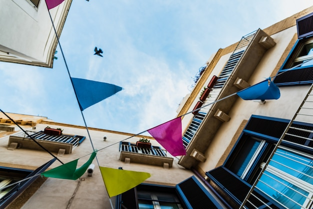 Colorful pennants seen from below crossing a street with old buildings.