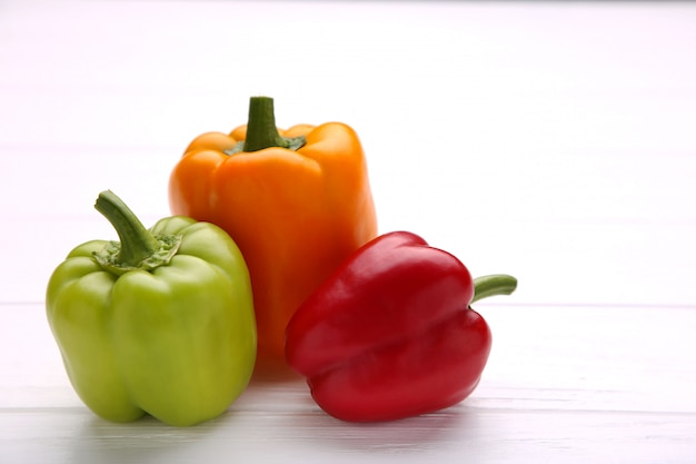 Colorful peppers on white wooden table. colorful paprika on wooden background