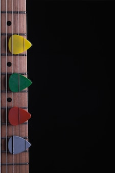 Colorful picks on neck of guitar