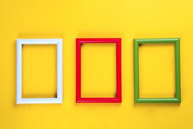 Colorful picture or photo frames on a yellow paper background. copyspace flat lay