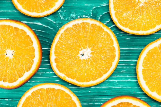 Colorful pieces of oranges on green background