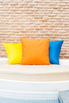 Colorful pillow on bed at hotel resort swimming pool