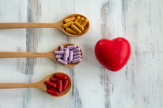 Colorful pills are in the spoon near rubber heart on white wooden table