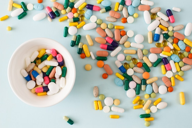 水色の背景の白いプレートにカラフルな錠剤、カプセル、サプリメント