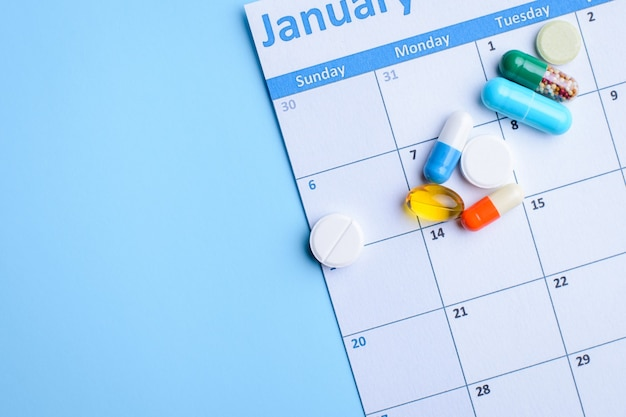 Colorful pills and capsules on calendar on light blue background