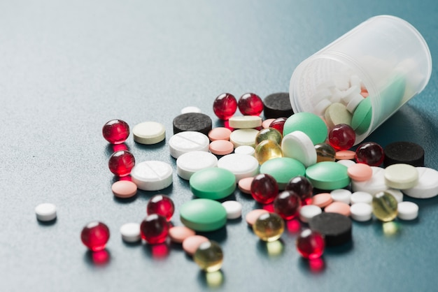 Colorful pills and capsules in cup