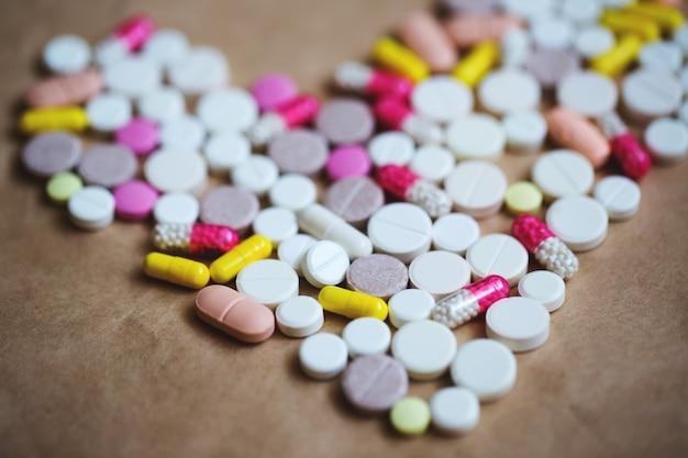 Красочные таблетки в форме сердца на бумаге