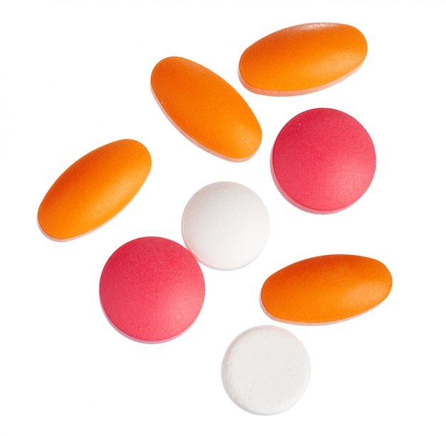 白で隔離されるカラフルな錠剤