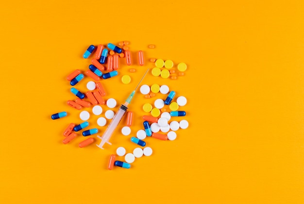 Colorful pills and needle